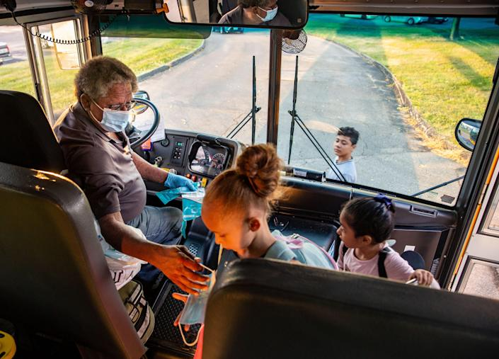 Des Moines, Iowa, school bus driver Jim Booker hands out masks as he picks up kids Sept. 14. Masks are required on school buses around the country, but that's a difficult rule to enforce.