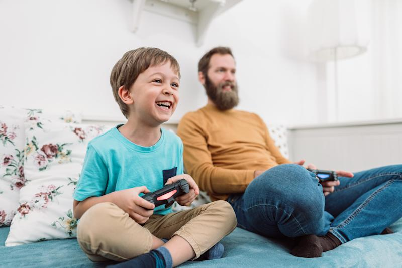 Cheerful little boy playing video games with his father at home