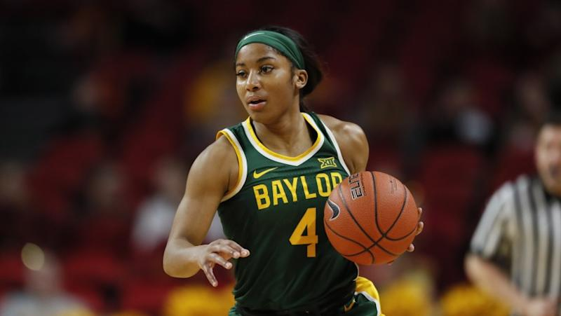 Baylor guard Te'a Cooper drives up court during an NCAA college basketball game.