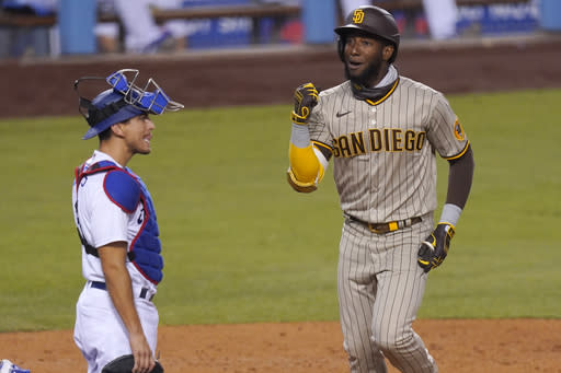 San Diego Padres' Jurickson Profar, right, celebrates as he scores after hitting a solo home run as Los Angeles Dodgers catcher Austin Barnes kneels at the plate during the fifth inning of a baseball game Tuesday, Aug. 11, 2020, in Los Angeles. (AP Photo/Mark J. Terrill)