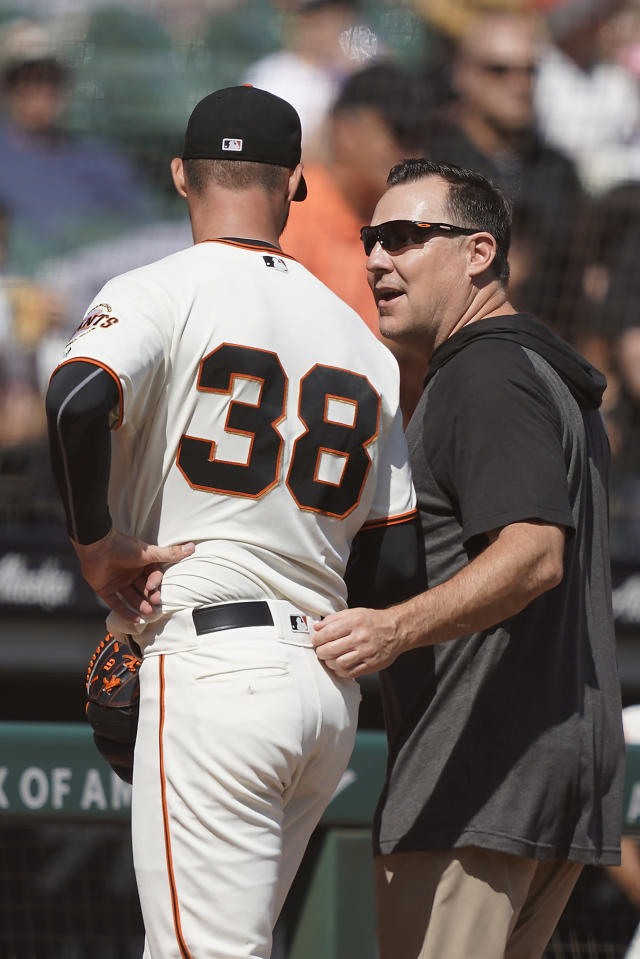 A trainer, right, walks off the field with San Francisco Giants pitcher Tyler Beede (38 who holds his side during the fourth inning of a baseball game against the Colorado Rockies Thursday, Sept. 26, 2019, in San Francisco. (AP Photo/Tony Avelar)