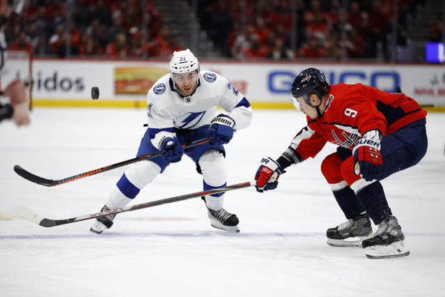Tampa Bay Lightning center Brayden Point, left, and Washington Capitals defenseman Dmitry Orlov, of Russia, chase the puck during the third period of an NHL hockey game Friday, Nov. 29, 2019, in Washington. Washington won 4-3 in overtime. (AP Photo/Patrick Semansky)