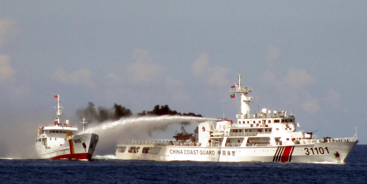 FILE - In this Sunday, May 4, 2014 file image made from video released by Vietnam Coast Guard, a Chinese coast guard vessel, right, fires water cannon at a Vietnamese vessel off the coast of Vietnam after China deployed an oil rig in disputed South China Sea waters. A top Chinese diplomat will visit Vietnam this week after China's deployment of a giant oil rig off Vietnam's coast in May increased tensions. (AP Photo/Vietnam Coast Guard, File)