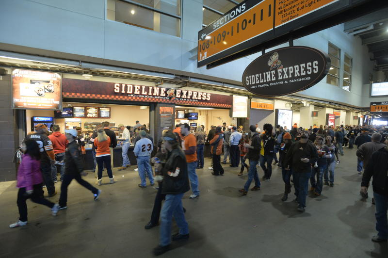 FILE - In this Oct. 12, 2014, file photo, fans walk past food concession stands prior to an NFL football game between the Cleveland Browns and the Pittsburgh Steelers, in Cleveland. The crippling coronavirus pandemic has brought the entire world — including the sports world — to a standstill, and it shows no sign of going away anytime soon. The Associated Press found during interviews with more than two dozen experts in stadiums and infrastructure that the only thing that might look the same is what happens on the field of play. The most obvious change in the short term will be the implementation of social distancing. Lines at restrooms and concessions will be limited. Congregating in the corridors will no longer be allowed. (AP Photo/David Richard, File)