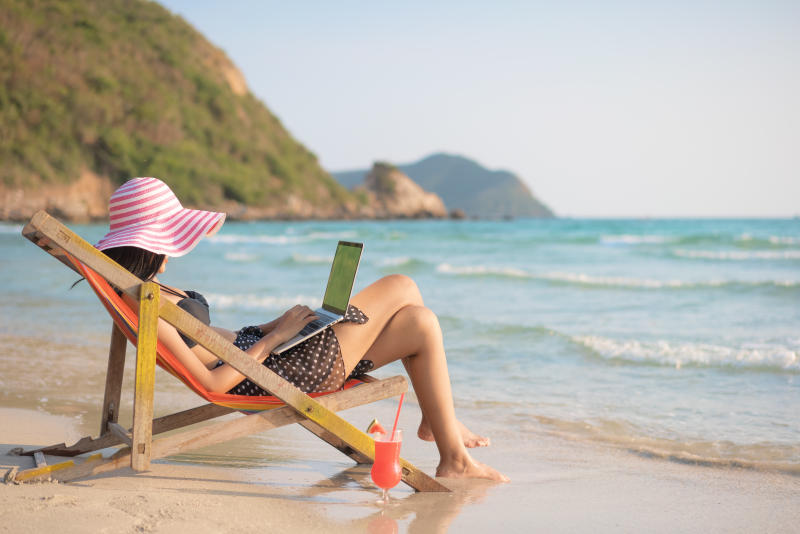 Young attractive woman in dress, sunglasses and hat, working in laptop on the beach