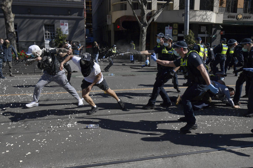 Police use pepper spray on protesters during an anti-lockdown protest in Melbourne, Australia, Saturday, Aug. 21, 2021. Protesters are rallying against government restrictions placed in an effort to reduce the COVID-19 outbreak. (James Ross/AAP Image via AP)