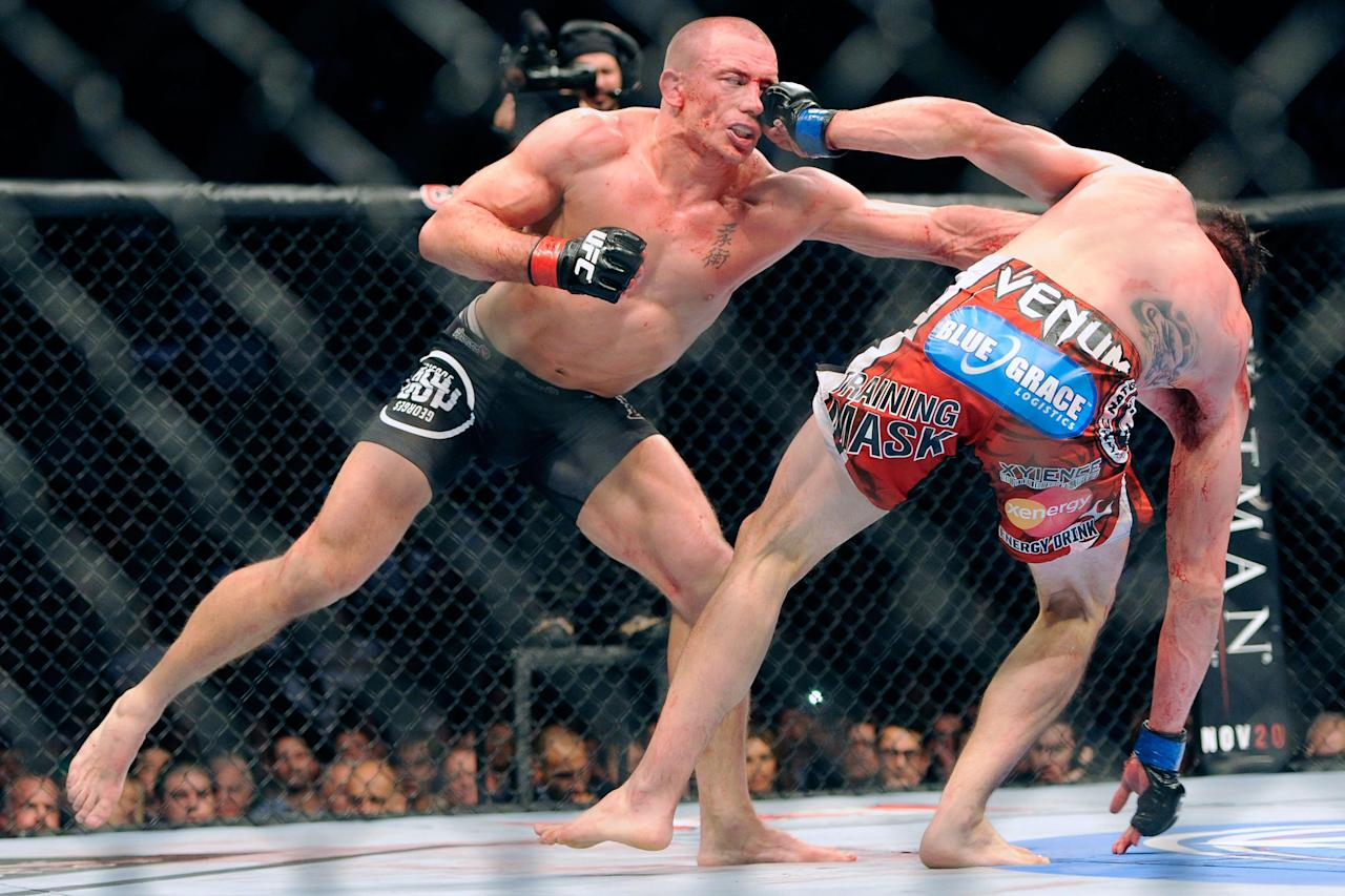 Nov 17, 2012; Montreal, QC, Canada;  Georges St-Pierre (black) lands a punch on Carlos Condit (red) during second round action of their Welterweight Championship bout at UFC 154 at the Bell Centre.  Mandatory Credit: Eric Bolte-US PRESSWIRE