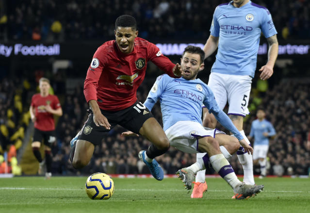 Manchester United's Marcus Rashford, left, duels for the ball with Manchester City's Bernardo Silva during the English Premier League soccer match between Manchester City and Manchester United at Etihad stadium in Manchester, England, Saturday, Dec. 7, 2019. (AP Photo/Rui Vieira)