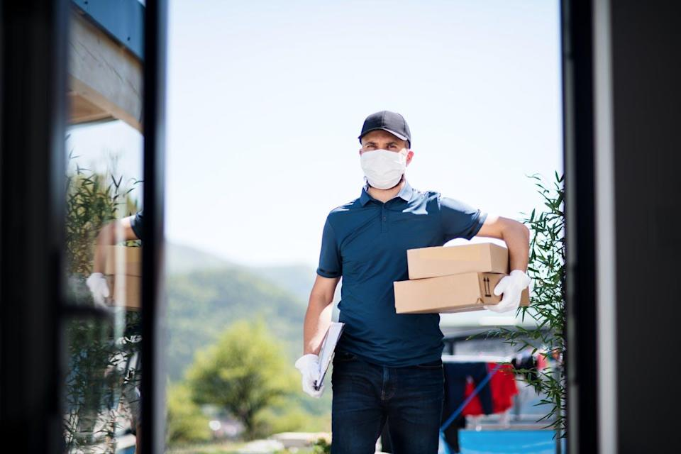 A man with a delivery box arrives at the door.