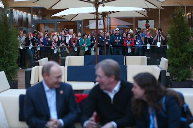SOCHI, RUSSIA - FEBRUARY 14: A crowd at the USA House watch as Russian President Vladimir Putin and U.S. Olympic Committee chairman Larry Probst visit USA House in the Olympic Village on February 14, 2014 in Sochi, Russia. (Photo by Marianna Massey/Getty Images for USOC)