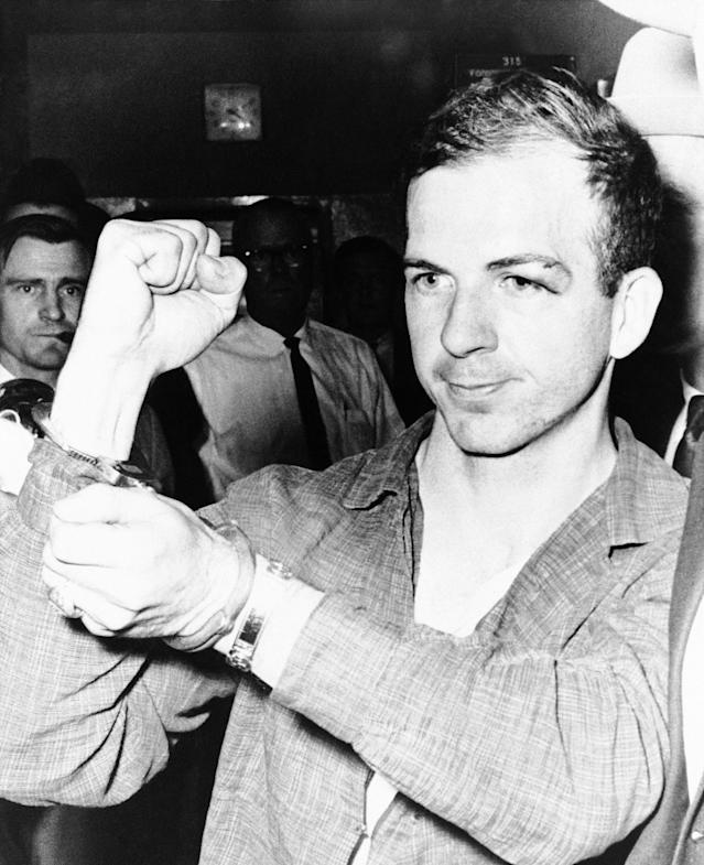 <p>Lee Harvey Oswald holds up his manacled hands as he is led thru the police station in Dallas on Nov. 22, 1963, where he was being held as a suspect in the assassination of President John Kennedy. He was charged with murder in the killing of a Dallas policeman who sought to arrest him in a theater several miles from the assassination scene. (Photo: AP) </p>
