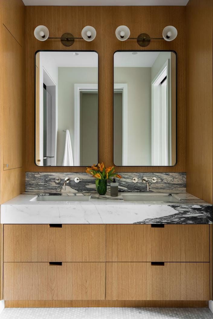 "<div class=""caption""> ""The master bathroom is my favorite space by far, and Gabriela, with the help of our architect <a href=""https://www.houzz.com/professionals/architects-and-building-designers/builtin-studio-pfvwus-pf~1040263976"" rel=""nofollow noopener"" target=""_blank"" data-ylk=""slk:BuiltIN Studio"" class=""link rapid-noclick-resp"">BuiltIN Studio</a>, perfectly synthesized my vision to create a hotel-like aesthetic,"" says Clayton. ""We wanted the millwork from the rest of the apartment to carry through so it felt extremely custom and, despite the clean and <a href=""https://www.rhmodern.com/catalog/product/product.jsp?productId=prod2701464&categoryId=search"" rel=""nofollow noopener"" target=""_blank"" data-ylk=""slk:minimal lines"" class=""link rapid-noclick-resp"">minimal lines</a> I desired, would still feel <a href=""https://www.benjaminmoore.com/en-us/color-overview/find-your-color/color/af-100/pashmina?color=AF-100"" rel=""nofollow noopener"" target=""_blank"" data-ylk=""slk:warm"" class=""link rapid-noclick-resp"">warm</a>."" </div>"