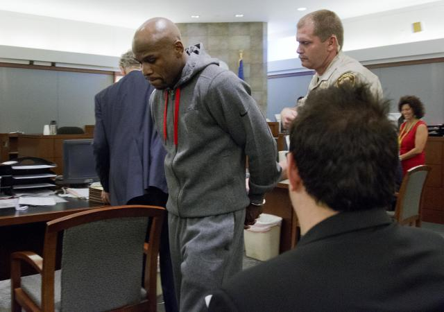 Floyd Mayweather Jr., left, is led away by court marshall Ron Johnson, Friday, June 1, 2012, in Las Vegas, to begin a 90-day jail term for attacking his ex-girlfriend in September 2010 while two of their children watched. The undefeated five-division champion surrendered Friday before the judge who sentenced him in December, and then allowed him to remain free long enough to headline a May 5 fight. (AP Photo/Julie Jacobson)