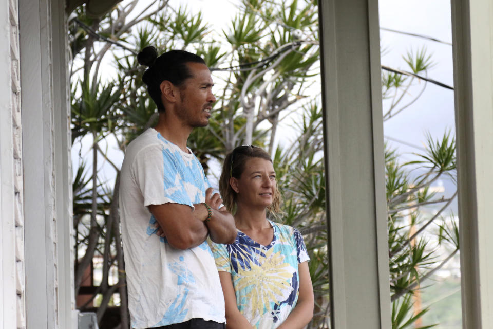 Matt Saunter, left, and Naomi Worcester stand on the porch of their home while under quarantine in Honolulu, Friday, Nov. 6, 2020. Cut off from the rest of the planet since February, Saunter, Worcester and two others are re-emerging from Kure Atoll in the Northwestern Hawaiian Islands, one of the most remote places on Earth, into a society changed by the coronavirus outbreak. Leading the camp on Kure was wildlife biologist Worcester and her partner, Saunter. (AP Photo/Caleb Jones)