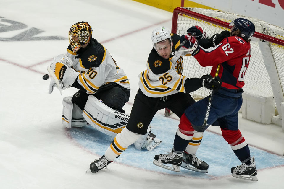 Boston Bruins goaltender Tuukka Rask (40) blocks a shot as Bruins defenseman Brandon Carlo (25) and Washington Capitals left wing Carl Hagelin (62) battle nearby during the second period of Game 2 of an NHL hockey Stanley Cup first-round playoff series Monday, May 17, 2021, in Washington. (AP Photo/Alex Brandon)
