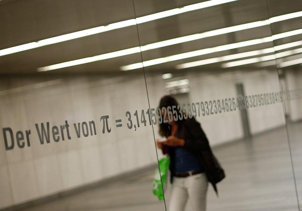 """A woman is reflected in a mirror with an inscription reading """"The value of Pi"""" and its numbers in Vienna  (AFP via Getty Images)"""