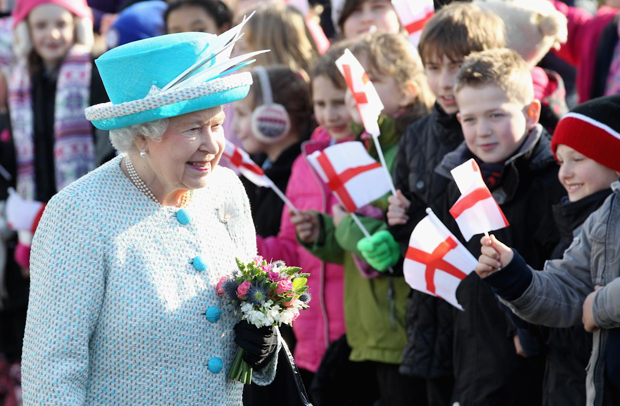 KING'S LYNN, ENGLAND - FEBRUARY 06:  Queen Elizabeth II smiles as children wave flags during a visit to Dersingham School on February 6, 2012 in King's Lynn, England. The Queen made the visit to the school as she celebrates Accession Day and 60 years on the throne.  (Photo by Chris Jackson/Getty Images)