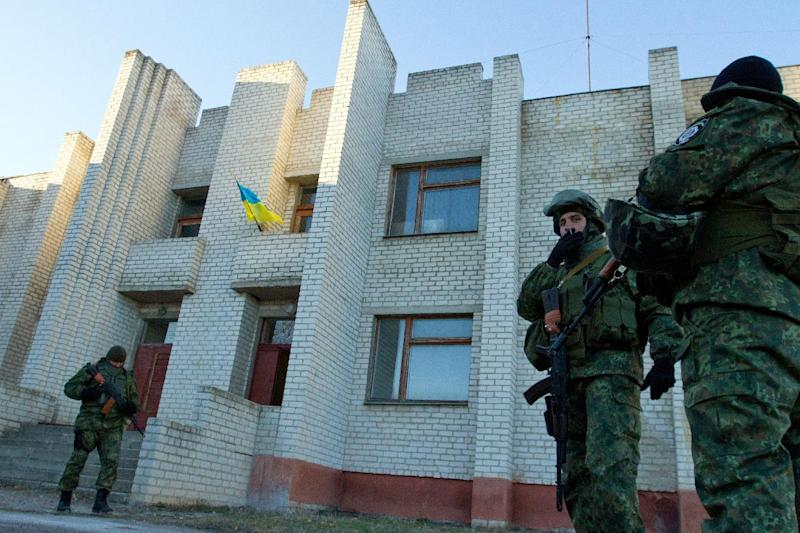 Ukrainian soldiers stand guard outside a polling station in Raygorodka village, Lugansk region on October 26, 2014 (AFP Photo/Anatolii Boiko)