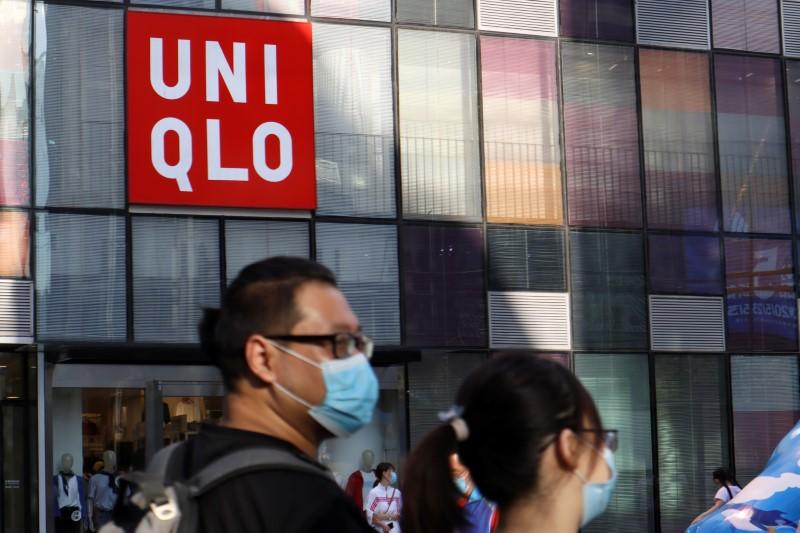 People walk past a store of the Fast Retailing's fashion chain Uniqlo, in Beijing