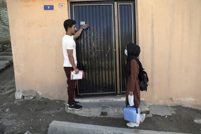 Health workers go door to door during a polio vaccination campaign in the city of Kabul, Afghanistan, Monday, March 29, 2021. Three female polio vaccinators were gunned down in separate attacks Tuesday in eastern Afghanistan, provincial officials said. (AP Photo/Rahmat Gul)