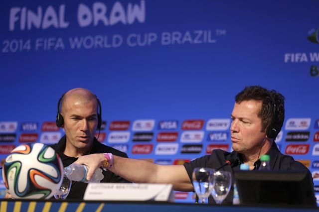 Former soccer great and World Cup winner Lothar Matthaeus of Germany, right, pours water into a glass as World Cup winner Zinedine Zidane of France looks on during a press conference one day before the draw for the 2014 soccer World Cup in Costa do Sauipe near Salvador, Brazil, Thursday, Dec. 5, 2013. (AP Photo/Andre Penner)