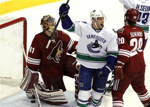 Vancouver Canucks' Ryan Kesler (17) celebrates a goal by teammate Alexander Edler against Phoenix Coyotes' Mike Smith (41) during the first period in an NHL hockey game, Tuesday, Feb. 28, 2012, in Glendale, Ariz. Coyotes' Chris Summers (20) skates in late to defend. (AP Photo/Ross D. Franklin)