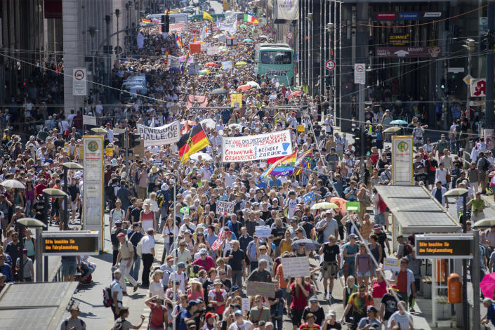 """Thousands march along the 'Friedrichstrasse' during the demonstration against corona measures in Berlin, Germany, Saturday, Aug. 1, 2020. The initiative """"Querdenken 711"""" has called for this. The motto of the demonstration is """"The end of the pandemic - Freedom Day"""". (Christoph Soeder/dpa via AP)"""