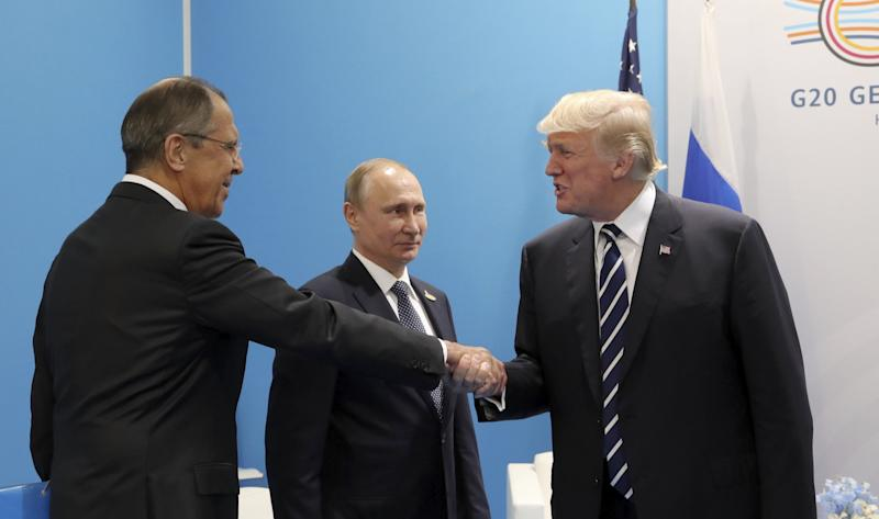 U.S. President Donald Trump shakes hands with Russian Foreign Minister Sergey Lavrov on July 7, 2017, as Russian President Vladimir Putin looks on.