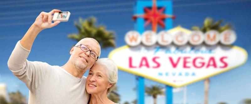 vacation, tourism and travel concept - happy senior couple hugging and taking photo by digital camera over welcome to fabulous las vegas sign background