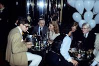 """<p>Yves Saint Laurent, Pierre Berger, and Andy Warhol at a party in """"le Palace"""" in 1977 in Paris, France.</p>"""