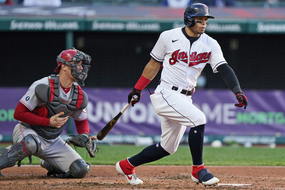 Cleveland Indians' Cesar Hernandez watches his three-run triple next to Cincinnati Reds catcher Tyler Stephenson the fourth inning of a baseball game Saturday, May 8, 2021, in Cleveland. (AP Photo/Tony Dejak)
