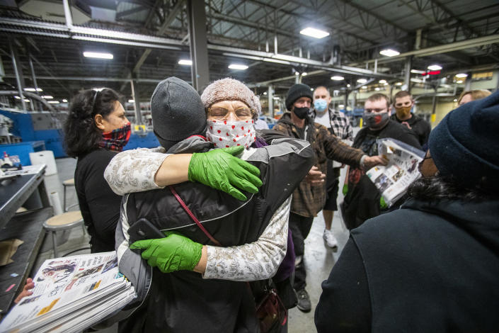 Employees talk and hug each other after the last daily edition of the Deseret News was printed at the MediaOne building in West Valley City, Utah, on Wednesday, Dec. 30, 2020. Both of Salt Lake City's major newspapers released their final daily print editions Thursday as the two publications transition to weekly editions. The Salt Lake Tribune, which won the Pulitzer Prize for local reporting in 2017, will continue to publish breaking stories online every day. The 170-year-old Deseret News in the state capital will also shift its attention online and offer a monthly magazine which will debut in January. (Scott G Winterton/The Deseret News via AP)