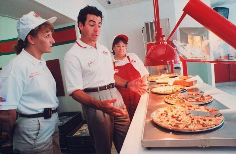 John Schnatter, founder & Pres. of a chain of Papa John's pizza restaurants, with employees at one of his outlets, making a surprise quality check on a row of pizzas laid out on counter at restaurant in 1997.
