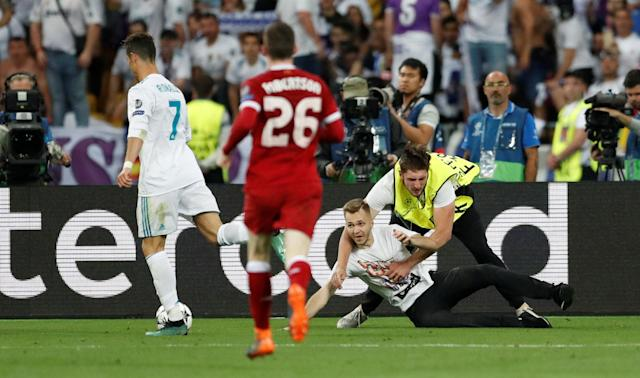 Soccer Football - Champions League Final - Real Madrid v Liverpool - NSC Olympic Stadium, Kiev, Ukraine - May 26, 2018 Real Madrid's Cristiano Ronaldo in action as a pitch invader is tackled by stewards REUTERS/Andrew Boyers