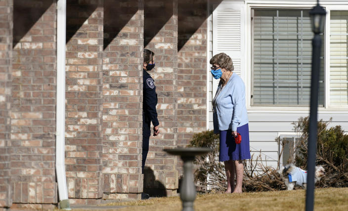 A police officer, left, talks to a resident as she walks her dog outside the front door of the Legacy Assisted Living at Lafayette care facility, Wednesday, Feb. 3, 2021, in Lafayette, Colo. A 95-year-old resident of the assisted care home was taken into police custody Wednesday after allegedly shooting an employee at the center. (AP Photo/David Zalubowski)