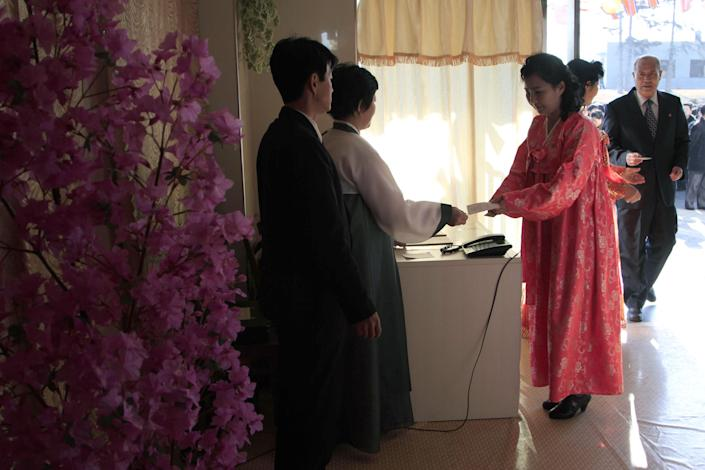 A woman receives a ballot to vote to elect deputies to the 13th Supreme People's Assembly in Pyongyang, North Korea Sunday, March 9, 2014. North Korean voters went to polling stations to elect a new national legislature, although they don't get to choose who to vote for since there is only one candidate per district. (AP Photo/Kim Kwang Hyon)