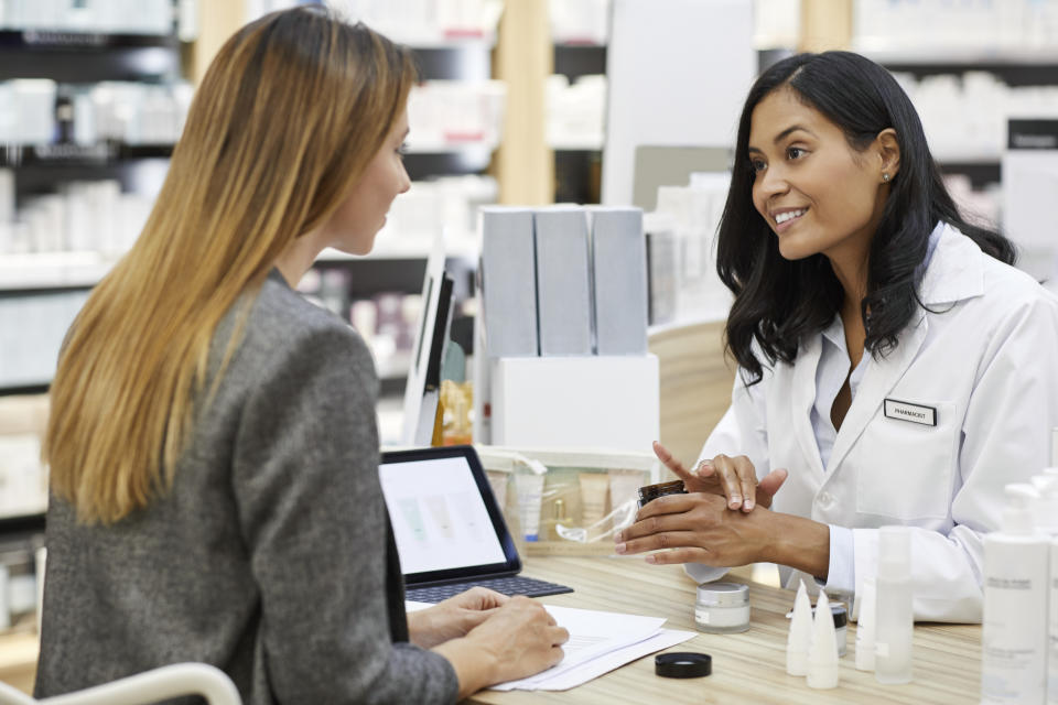 Smiling pharmacist checking medical sample while talking to a woman at checkout.