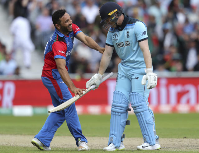 Afghanistan's captain Gulbadin Naib, left, shares a light moment with England's captain Eoin Morgan after an unsuccessful run-out attempt during the Cricket World Cup match between England and Afghanistan at Old Trafford in Manchester, England, Tuesday, June 18, 2019. (AP Photo/Rui Vieira)