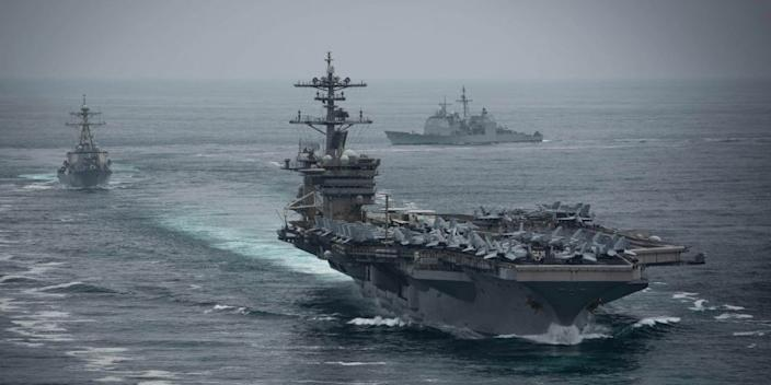 The aircraft carrier USS Theodore Roosevelt (CVN 71), front, the Arleigh Burke-class guided-missile destroyer USS Russell (DDG 59), left, and the Ticonderoga-class guided-missile cruiser USS Bunker Hill (CG 52), transit in formation.