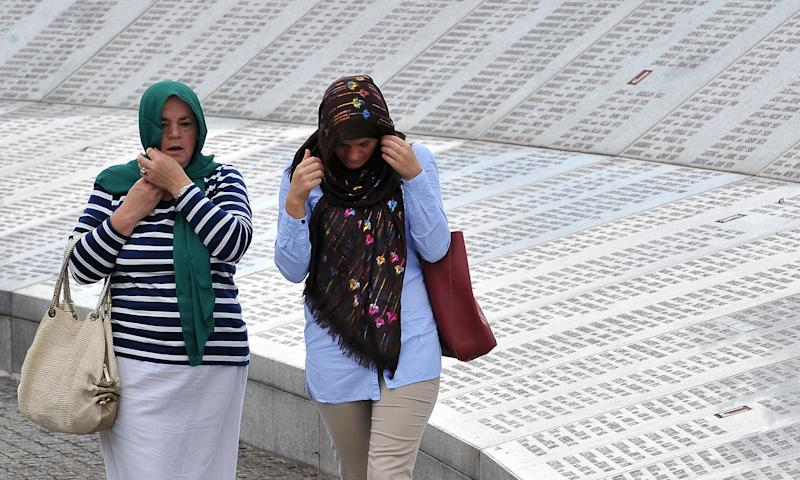 A Bosnian Muslim woman, survivor of the Srebrenica 1995 massacre searches for names of her relatives among names of victims, engraved on a Memorial Wall at Srebrenica Memorial cemetery in Potocarion near Srebrenica, on July 10, 2014 (AFP Photo/Elvis Barukcic)
