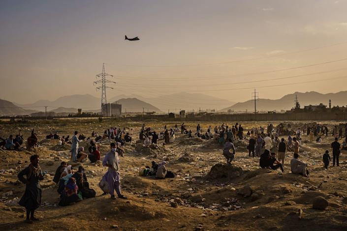 a helicopter flies over people standing in the hazy desert with mountains in the far distance