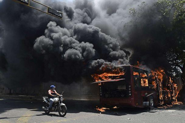 PHOTO: An opposition demonstrator passes by a government bus set on fire during clashes with soldiers loyal to Venezuelan President Nicolas Maduro after troops joined opposition leader Juan Guaido in his campaign to oust Maduro in Caracas, April 30, 2019. (Federico Parra/AFP/Getty Images)