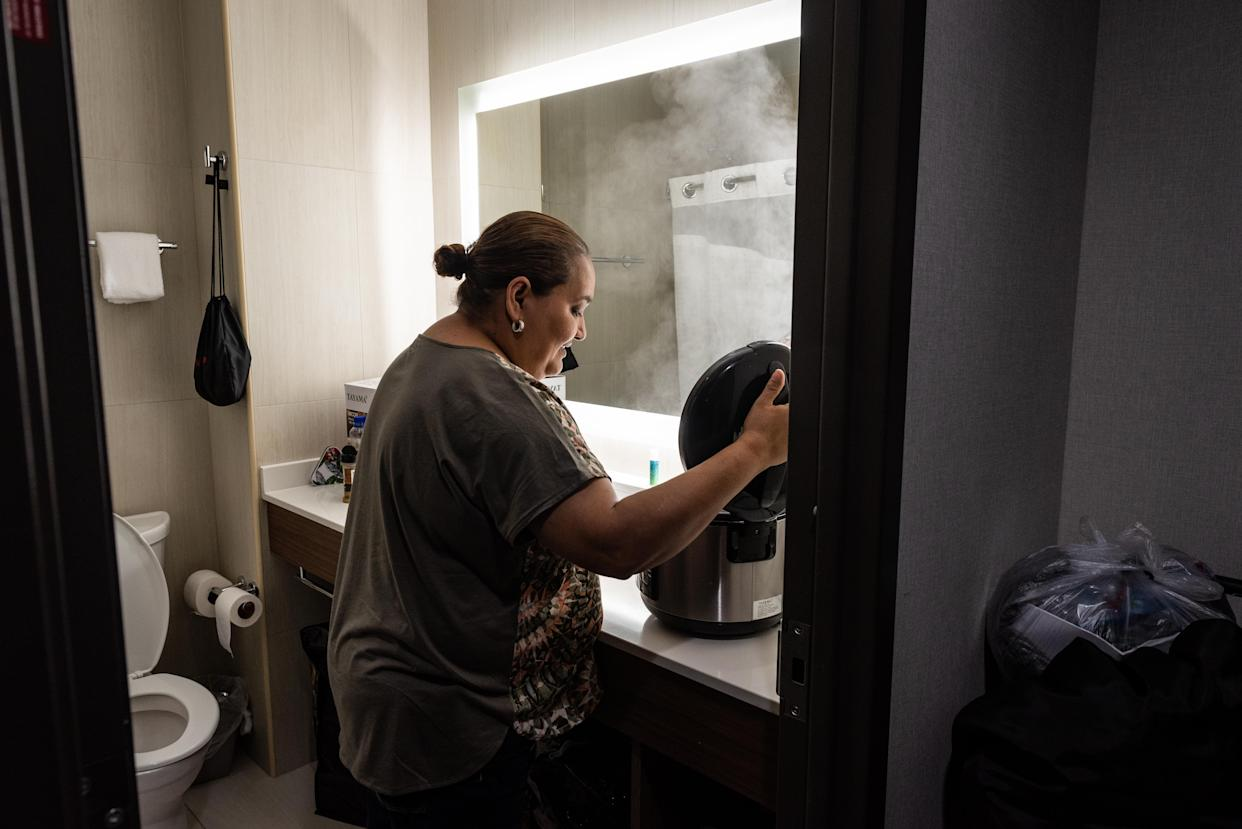 "<span class=""s1"">Jenyffer Ortiz cooks chicken in a rice cooker in the hotel bathroom, where there is counter space. She cooks for herself to better deal with diabetes and other ailments. (Photo: David ""Dee"" Delgado for Yahoo News)</span>"