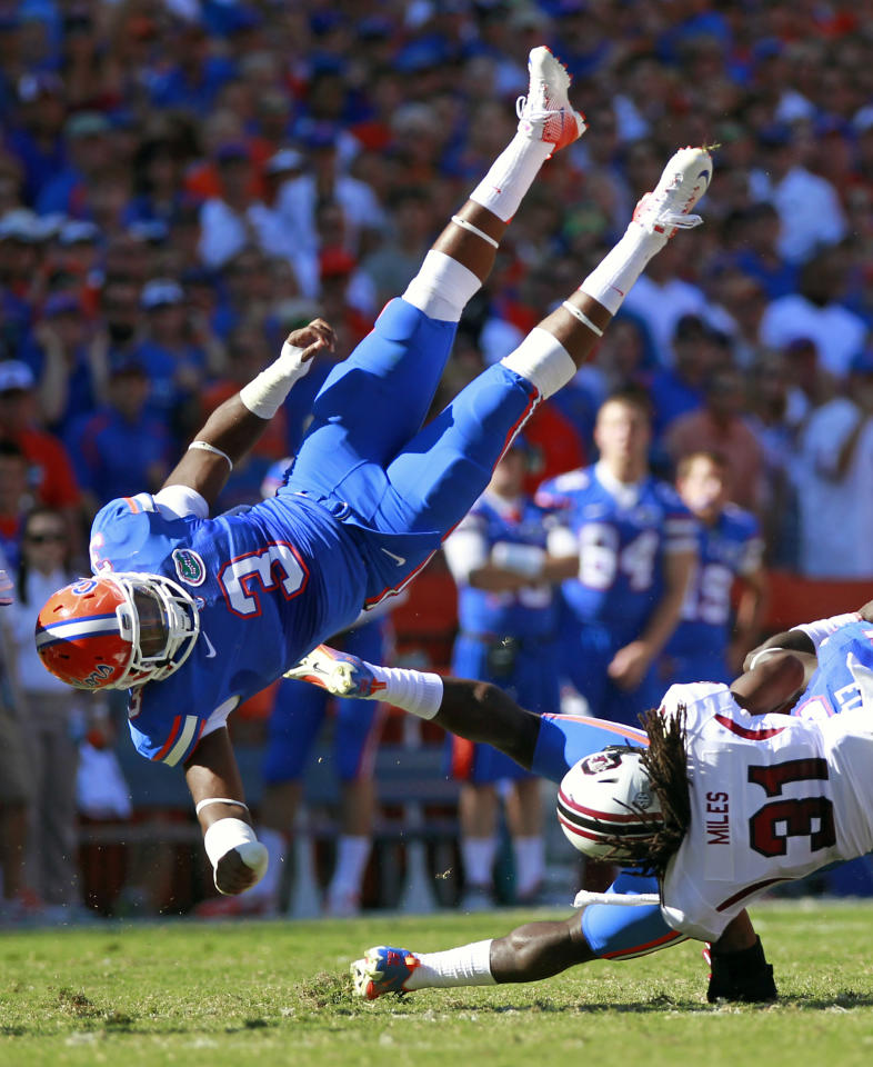 Florida linebacker Jelani Jenkins (3) goes airborne after assisting on a tackle on South Carolina's Kenny Miles (31) during the first half of an NCAA college football game, Saturday, Oct. 20, 2012, in Gainesville, Fla. (AP Photo/John Raoux)