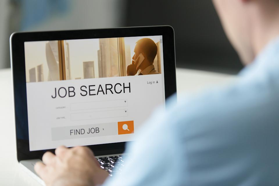 Monitor view over a male shoulder, job search title on the screen, close up.