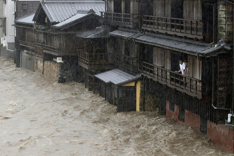 People watch the Isuzu River swollen by Typhoon Hagibis, in Ise, central Japan Oct. 12, 2019. (Photo: Kyodo News via AP)