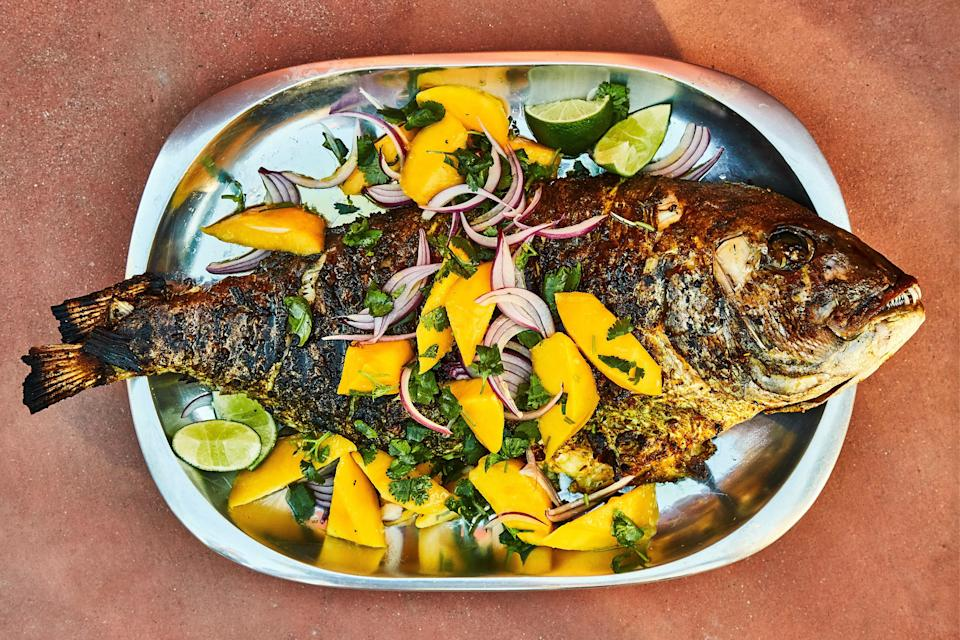 """Hosting your seder outside this year? Then you might as well use the grill. A whole fish makes an impressive—but actually easy—main dish. <a href=""""https://www.epicurious.com/recipes/food/views/grilled-spiced-snapper-with-mango-and-red-onion-salad?mbid=synd_yahoo_rss"""" rel=""""nofollow noopener"""" target=""""_blank"""" data-ylk=""""slk:See recipe."""" class=""""link rapid-noclick-resp"""">See recipe.</a>"""