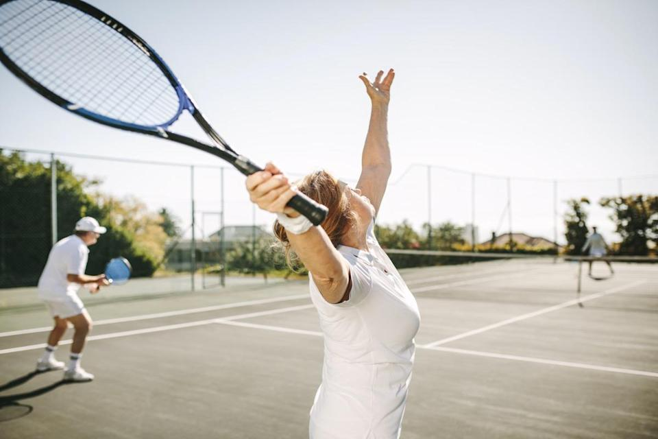 woman serving the ball while playing a mixed doubles tennis match