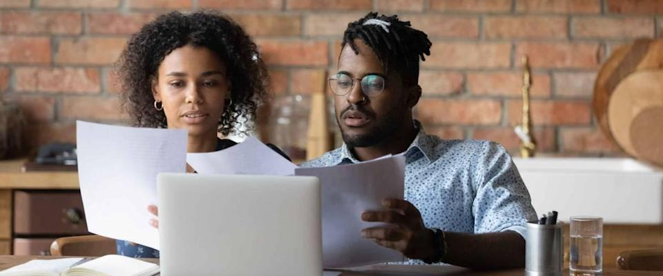 Focused Black couple researching mortgage offers.