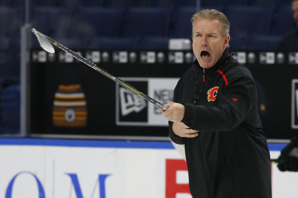 Calgary Flames associate coach Geoff Ward gives instruction during an NHL hockey practice Tuesday, Nov. 26, 2019, in Buffalo, N.Y. Flames general manager Brad Treliving says coach Bill Peters remains on the staff but wasnt certain whether hed be behind the bench for the next game. The team and the NHL are both investigating an allegation the Peters directed racial slurs at a player 10 years ago when the two were in the minors. Akim Aliu, a Nigerian-born player, says Peters dropped the N bomb several times in a dressing room during his rookie year. (AP Photo/Jeffrey T. Barnes)